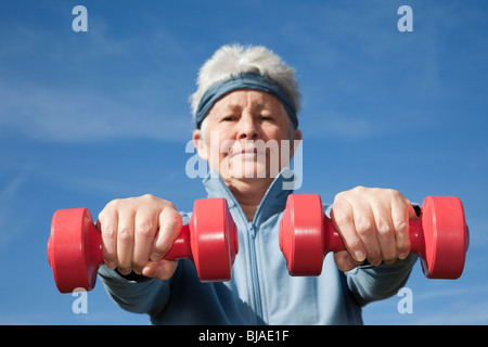 Active senior woman exercising with dumbbell hand weights workout outdoors to keep fit. Healthy lifestyle wellness - Stock Photo