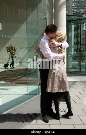 young couple embracing outside glass office building - Stock Photo