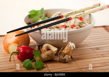 vegetarian ramen noodles dish, chopsticks at rest on bowl, ingredients in foreground - Stock Photo