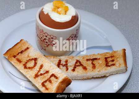 Generic image of Marmite with Love and Hate written on toast.  A Unilever Brand guaranteed to cause arguments. - Stock Photo
