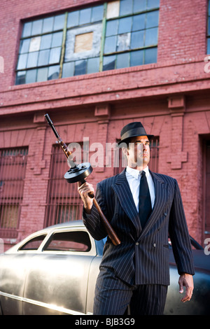 Gangster holding Tommy  gun on lookout - Stock Photo