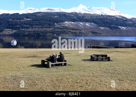 Winter picnic on the banks of Loch Lomond with a snow capped Ben Lomond in the background - Stock Photo