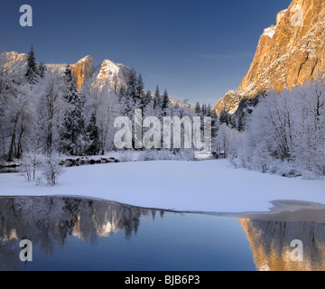 Three Brothers face and Cathedral Spires reflected in the Merced River after a snowfall in Yosemite National Park - Stock Photo
