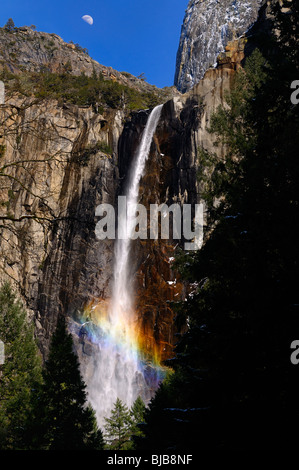 Rainbow in the mist of Bridalveil Fall waterfalls at Cathedral Rocks with half moon Yosemite National Park California - Stock Photo