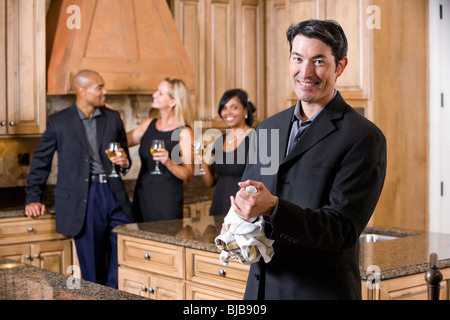 Man with champagne bottle in kitchen, group of friends chatting in background - Stock Photo