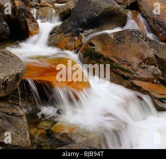 Red rock in waterfall rapids on Bridalveil Creek below the Fall in Yosemite Valley Yosemite National Park California - Stock Photo