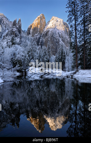 Cathedral Rocks and Spires reflected in the Merced River after a snowfall in winter Yosemite National Park California - Stock Photo