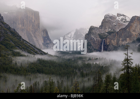 Clouds and fog in Yosemite Valley with Bridalveil Fall after a winter rain storm seen from Tunnel View Yosemite - Stock Photo