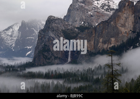 Bridalveil Fall waterfall emptying into clouds and fog in Yosemite Valley after a winter storm seen from Tunnel - Stock Photo