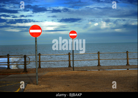 No entry road sign by sea wall - Stock Photo