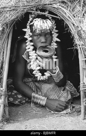 Mursi Tribe Girl With Lip Plate Sat In The Doorway To Her Hut, Omo Valley, Ethiopia - Stock Photo