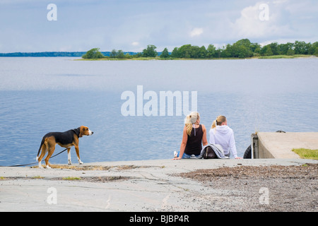 Two blond girls and a dog waiting for a passenger boat in the 'Archipelago of Stockholm' Sweden. - Stock Photo