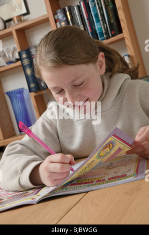 Ten year old girl with comic in front of bookshelves. - Stock Photo