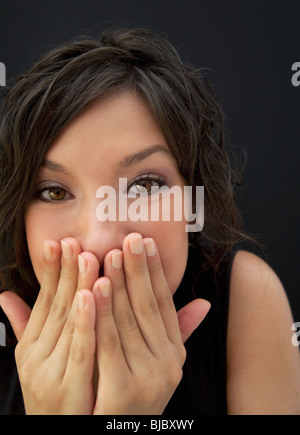 Surprised Hispanic woman with hands covering face - Stock Photo