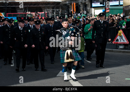 A piper leading a parade of fire fighters during the St Patricks Day Parade in London. - Stock Photo