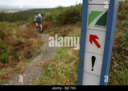Mountain biker rides past a warning sign on a 7stanes trail in Scotland - Stock Photo