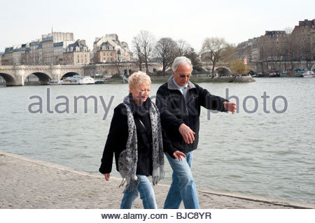 Senior couple walking along Seine river, Paris, France, - Stock Photo