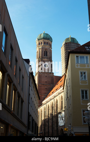 The clock towers of St Peters Church (Peterskirche) in Munich, Germany, as seen from between the buildings - Stock Photo