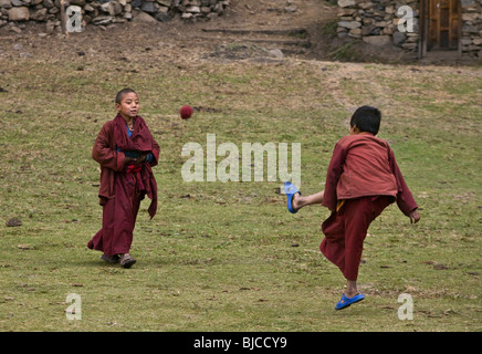 Young MONKS play soccer at a remote TIBETAN BUDDHIST MONASTERY - NEPAL HIMALAYA - Stock Photo