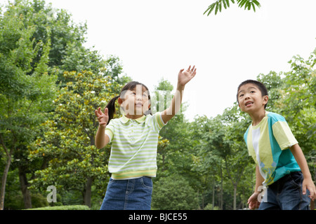 Young Boy and Girl having fun in The Park - Stock Photo