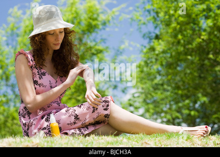Young woman in sun hat sitting outdoors, applying sunscreen - Stock Photo