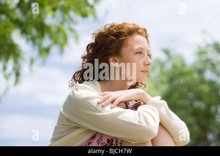 Young woman outdoors, looking away in thought - Stock Photo