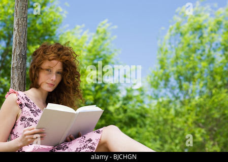 Young woman reading outdoors, portrait - Stock Photo