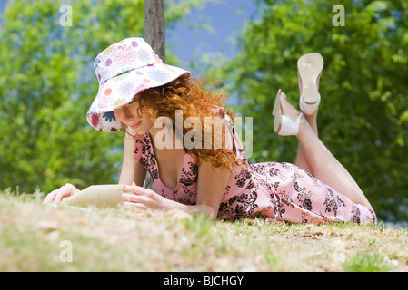 Young woman lying on stomach reading outdoors - Stock Photo