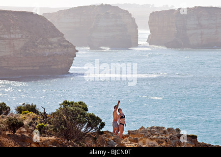 A couple having fun with Great Ocean Road landscape cliffs in the background, South Australia - Stock Photo