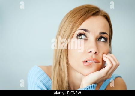 portrait of woman thinking and biting her lips, looking up with hand on cheek. Horizontal shape, Copy space - Stock Photo