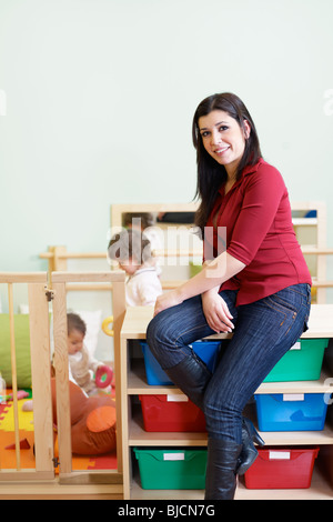 portrait of mid adult teacher in kindergarten. Little girls playing with toys in background. Vertical shape, copy - Stock Photo