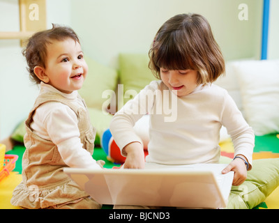 female toddler and 2-3 years old girl playing with pc in kindergarten. Horizontal shape - Stock Photo