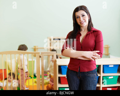 portrait of mid adult teacher in kindergarten. Little girls playing with toys in background. Horizontal shape, copy - Stock Photo