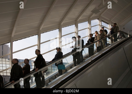 Urban living space building ; people standing on automatic staircase in exhibition center ; Frankfurt ; Germany - Stock Photo