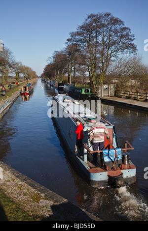 Narrowboat leaving a lock on the Trent and Mersey Canal at Fradley, Staffordshire - Stock Photo