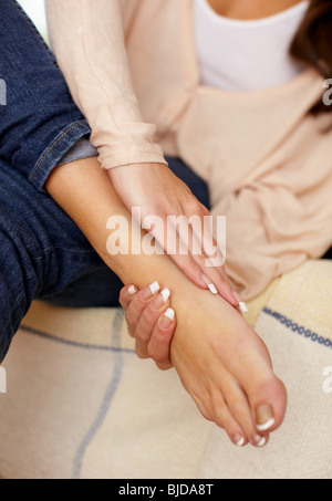 Woman massaging aching feet - Stock Photo