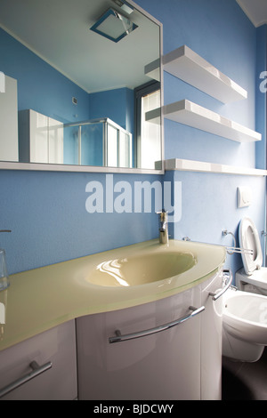 Modern white cabinets shiny polished in bathroom belonging to a studio apartment - Stock Photo