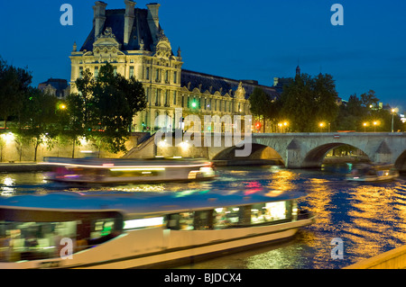 Paris, France - Outside Nighttime View of the Seine River with Louvre Museum and Passing Tourist Boats - Stock Photo