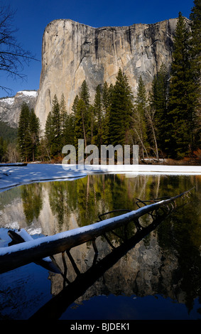 El Capitan mountain reflected in the Merced River in winter from Cathedral beach with a snow covered log in Yosemite - Stock Photo