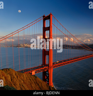 Red Golden Gate Bridge with San Francisco skyline and moon at sunset California USA - Stock Photo