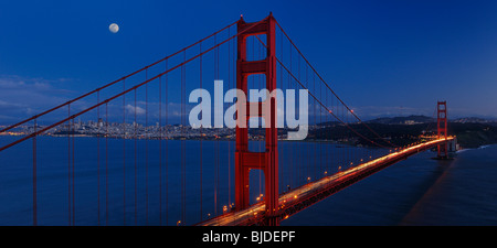 Panorama of Golden Gate Bridge and San Francisco skyline at twilight with rising moon California USA - Stock Photo