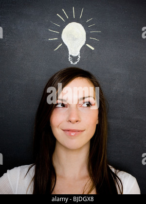 young woman against a chalkboard - Stock Photo