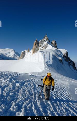 Snowboarder walking on narrow ridge from Aiguille du Midi towards Le Vallee Blanche, Chamonix, France - Stock Photo
