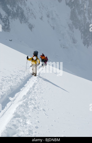 Snowboarder and skiers ascending a snowy slope in glaciated terrain above The Vallee Blanche, Chamonix, France - Stock Photo