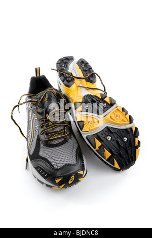 Water-proof running shoes with spikes for traction on snow and ice - Stock Photo