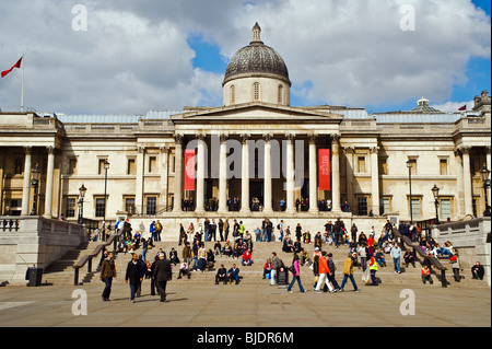 A busy scene on the steps of the National Gallery in Trafalgar Square, London - Stock Photo