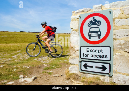 Female mountain biker rides past sign barring motor vehicles on Clapham Lane, a green lane  in the Yorkshire Dales, - Stock Photo