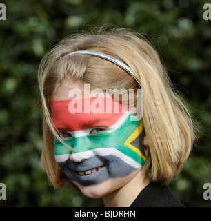 Portrait of a girl with face painted in the colours of the national flag of South Africa