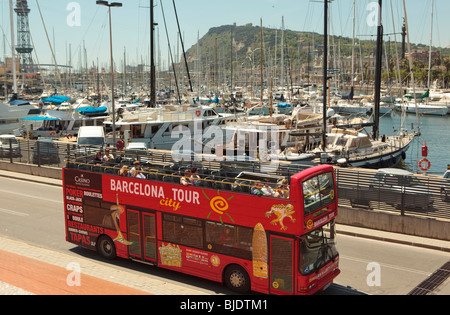 Tourists get a top deck view of boats in Barcelona Harbour from a red open top tour bus. - Stock Photo