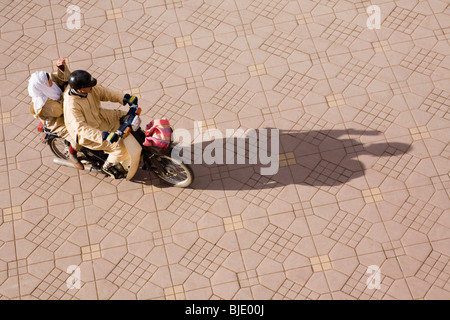 Marrakech Morocco North Africa. Aerial view of long shadow of two Moroccan people riding moped in Place Djemma el - Stock Photo